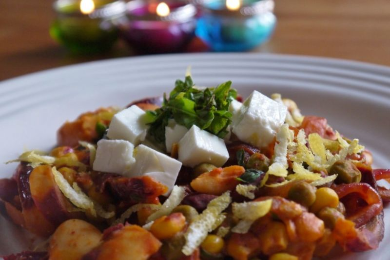 Harissa, kidney bean and chickpea one-pot dinner with feta and fresh herbs on a plate