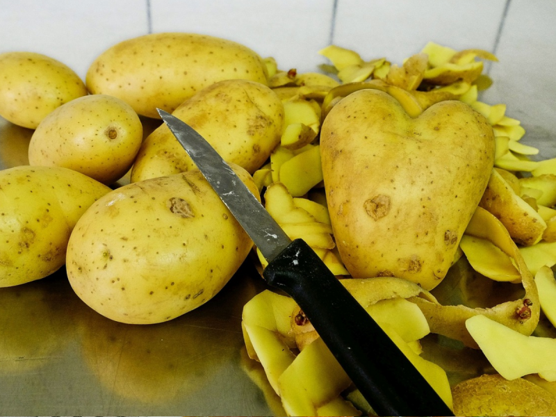 Some lovely potatoes with their peelings and a potato knife