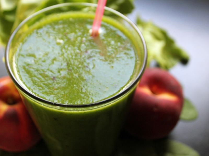 Green vegetable smoothie in glass with fruit next to it