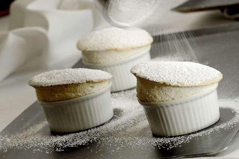 Hot banana souffles dusted with icing sugar in rammekins