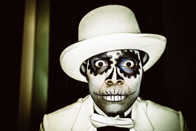 Close-up of a man in a Day of The Dead outfit in white bow tie, hat and coat with ghoulish face paint