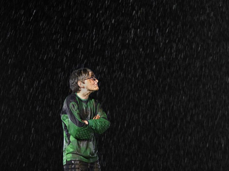 A boy wearing a dirty football kit in the rain