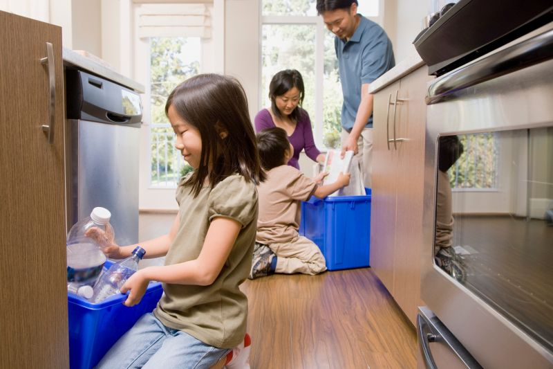 Family in kitchen recycling paper and plastic
