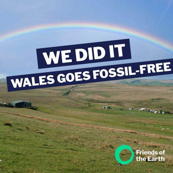 Rainbow over green flatlands with large text saying We Did It - Wales goes fossil free