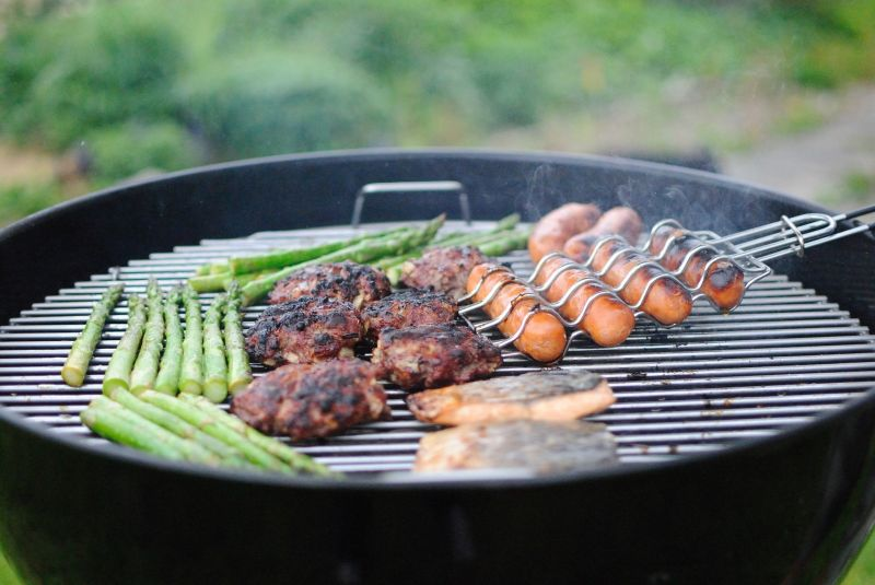 Barbecue grill with burgers, sausages and asparagus