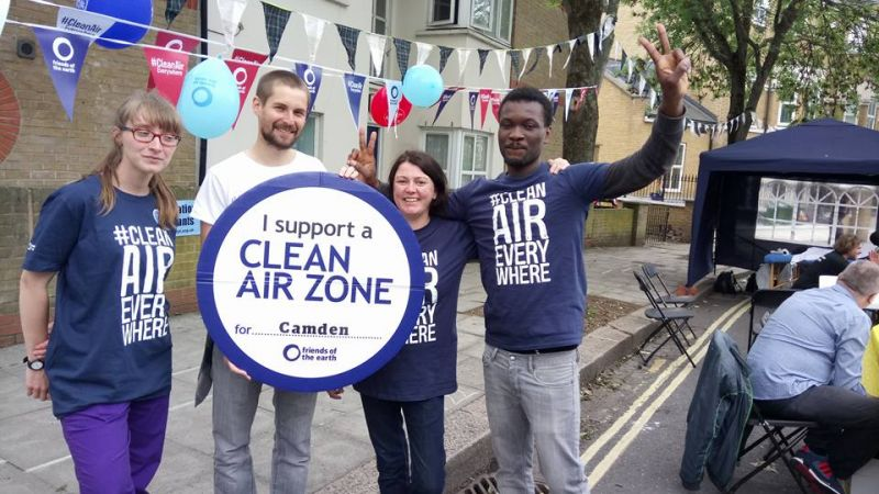 Camden Friends of the Earth. Clean Air Week of Action stall in street with people holding Clean Air Zone sign.