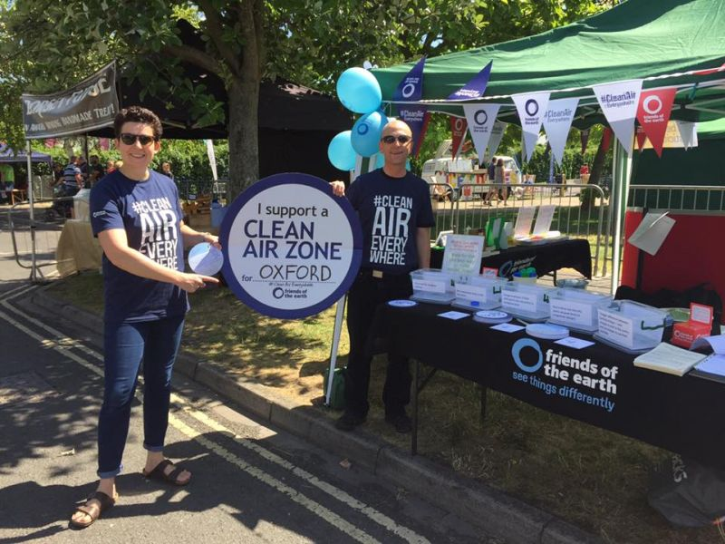 Two people holding a Clean air zone sign for Oxford