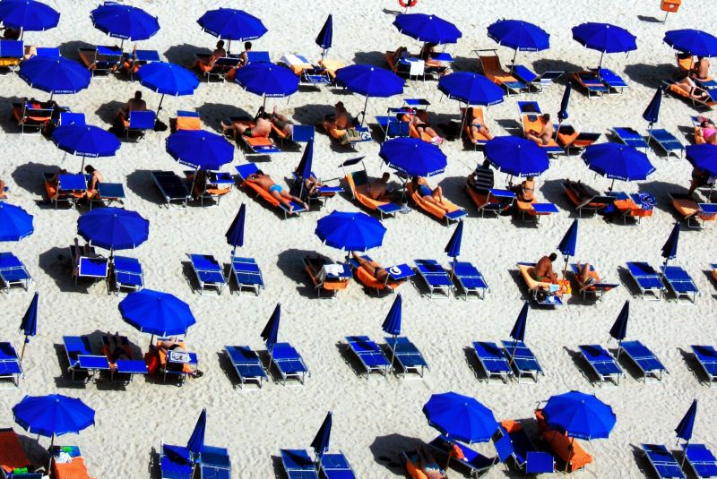 Blue sunloungers and blue umbrellas on white sands on a hot day.