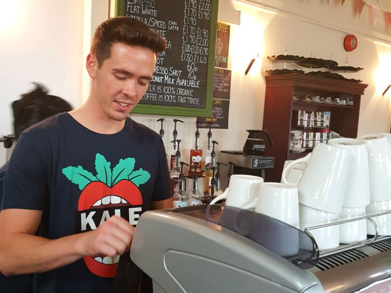 A member of staff wearing a Kale Yeah! t-shirt serving students at a coffee bar counter at Portsmouth University