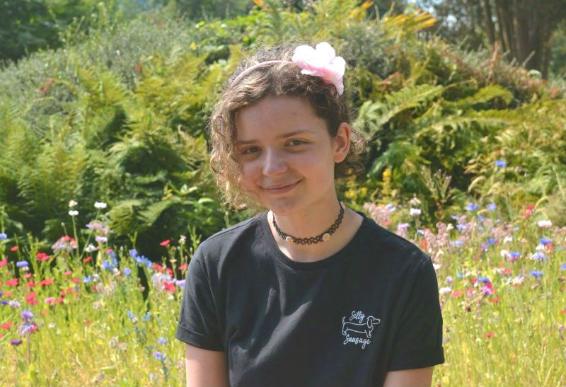 Teenager Leela Churchill facing camera in nature with ferns and wild flowers behind her.