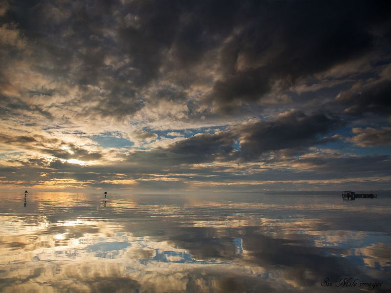 A cloudy blue sky is reflected in Lough Neagh