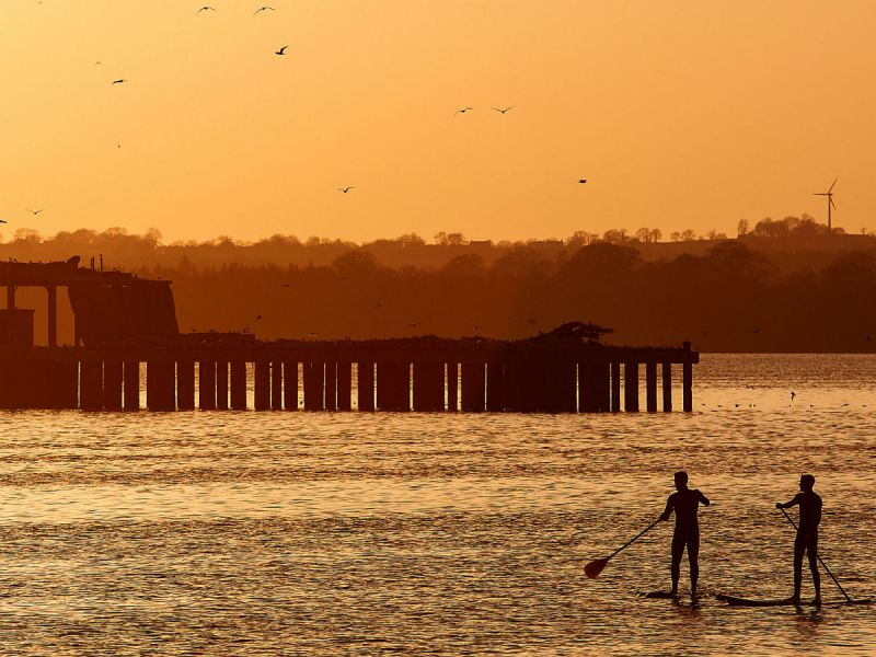 Two silhouetted figures at sunset doing stand-up paddling in front of a derelict torpedo-testing platform in Lough Neagh