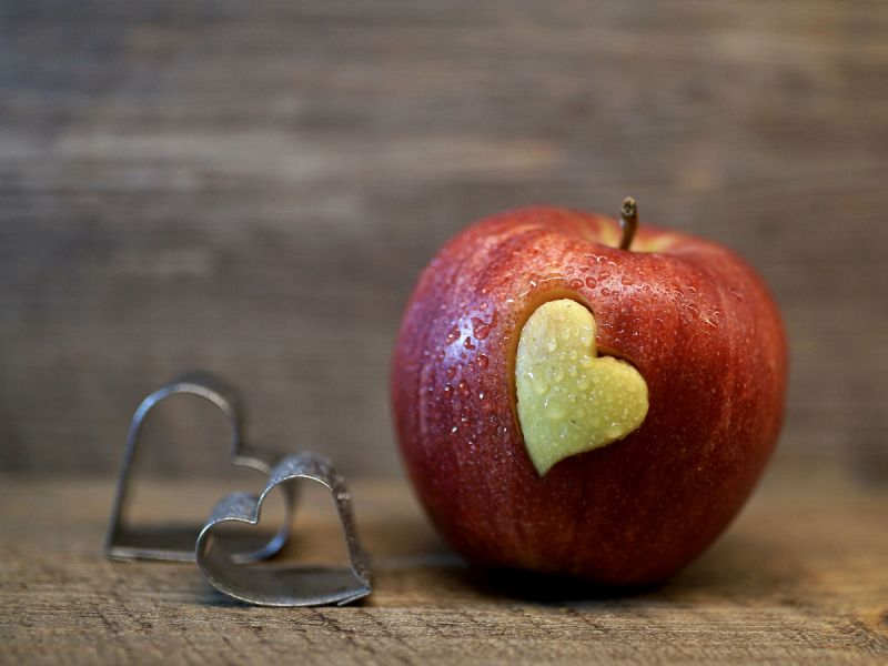 A red apple with a love heart shape carved out of the skin