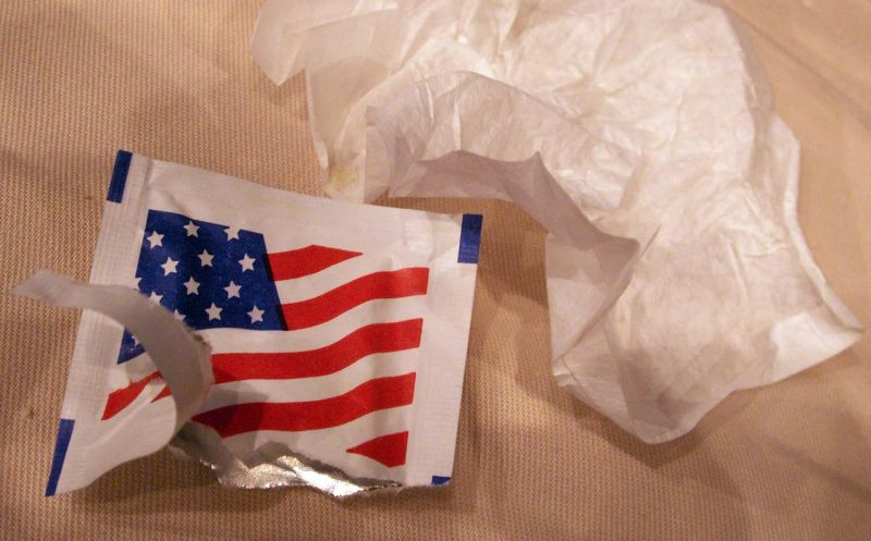 "A wet wipe, or ""moist towelette"", removed from its US-flag sachet"