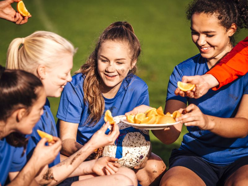 Girls sports team eating oranges at half time