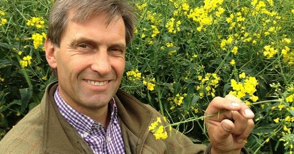 "Casually dressed ""green"" farmer Peter Lundgren with background of yellow flowers."