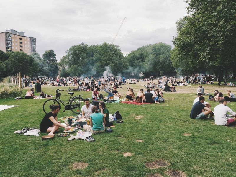 People picnicking and barbecuing in park in hot weather
