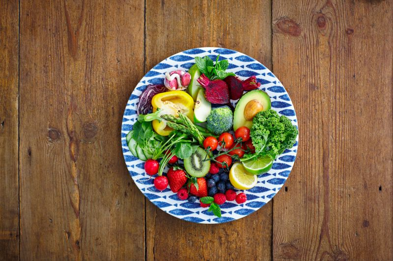 healthy fruits and vegetables salad served on a plate on wooden counter