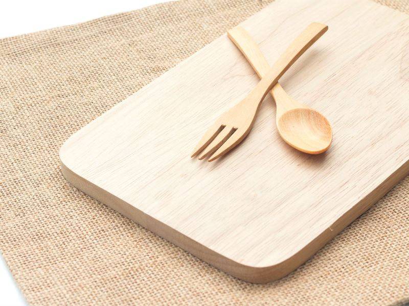 A spoon and a fork on a wooden chopping board