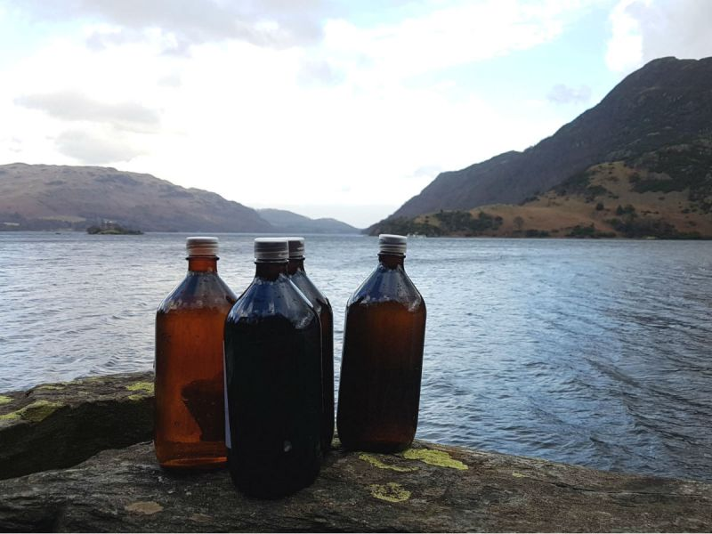 Four full 1-litre bottles placed on a rock next to Ullswater Lake in the Lake District