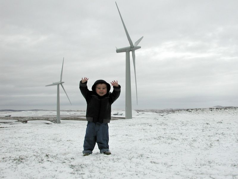 A little boy called Ben stands in front of 2 wind turbines at a Welsh community-owned wind farm