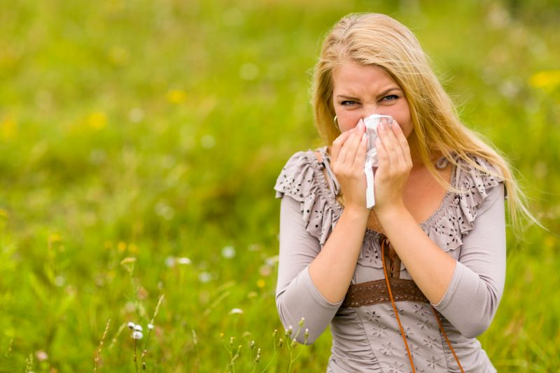 Young white woman in field blowing her nose.