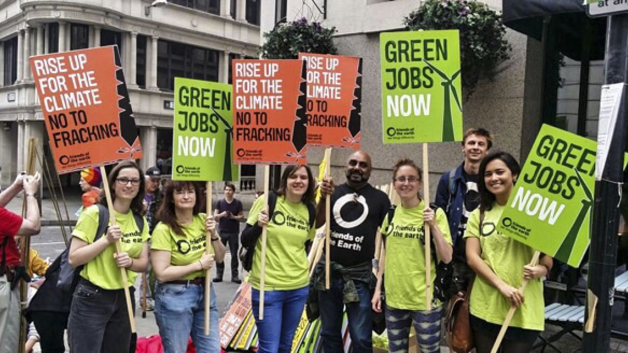 Activists holding signs supporting green jobs and against fracking