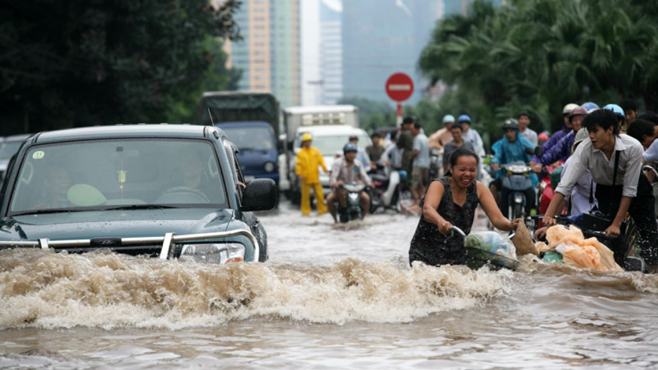 Cyclists struggle to push their bikes through the floodwater in Hanoi, China