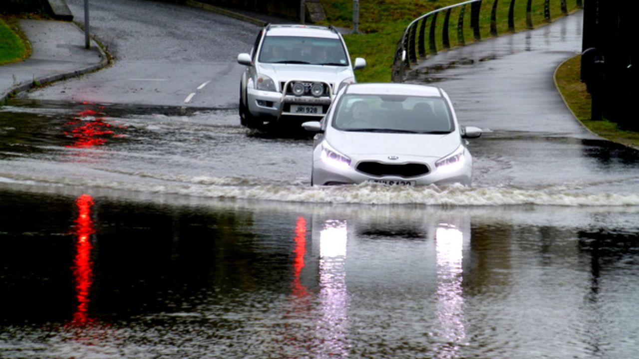 2 cars enter a heavily flooded road in Omagh, Northern Ireland