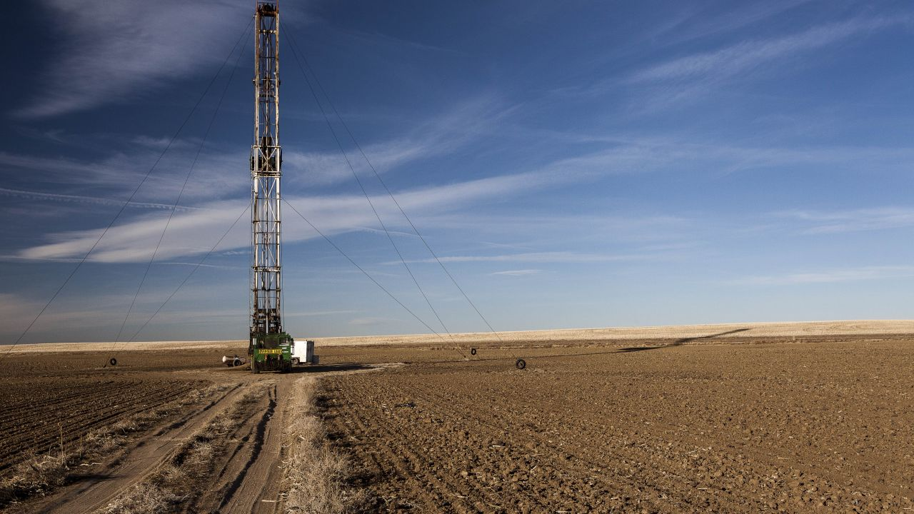 Fracking rig surrounded by barren flatland of dry soil