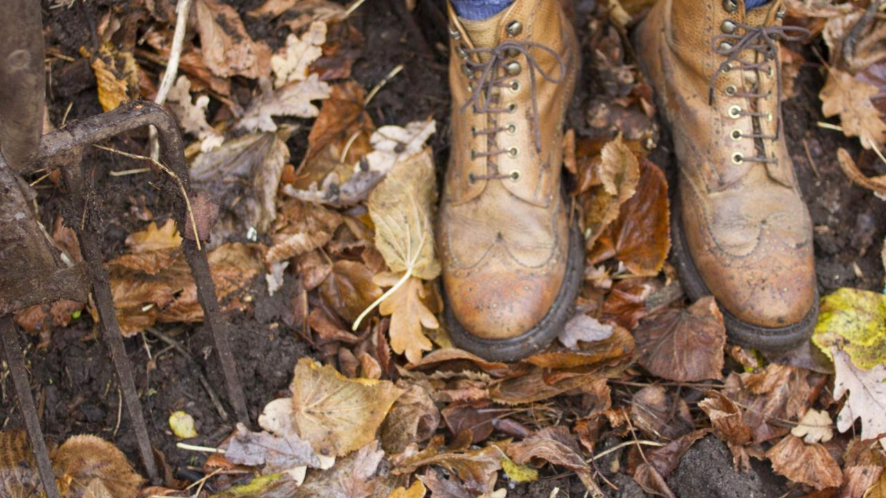 Rotting leaves on ground, with garden fork and shoes