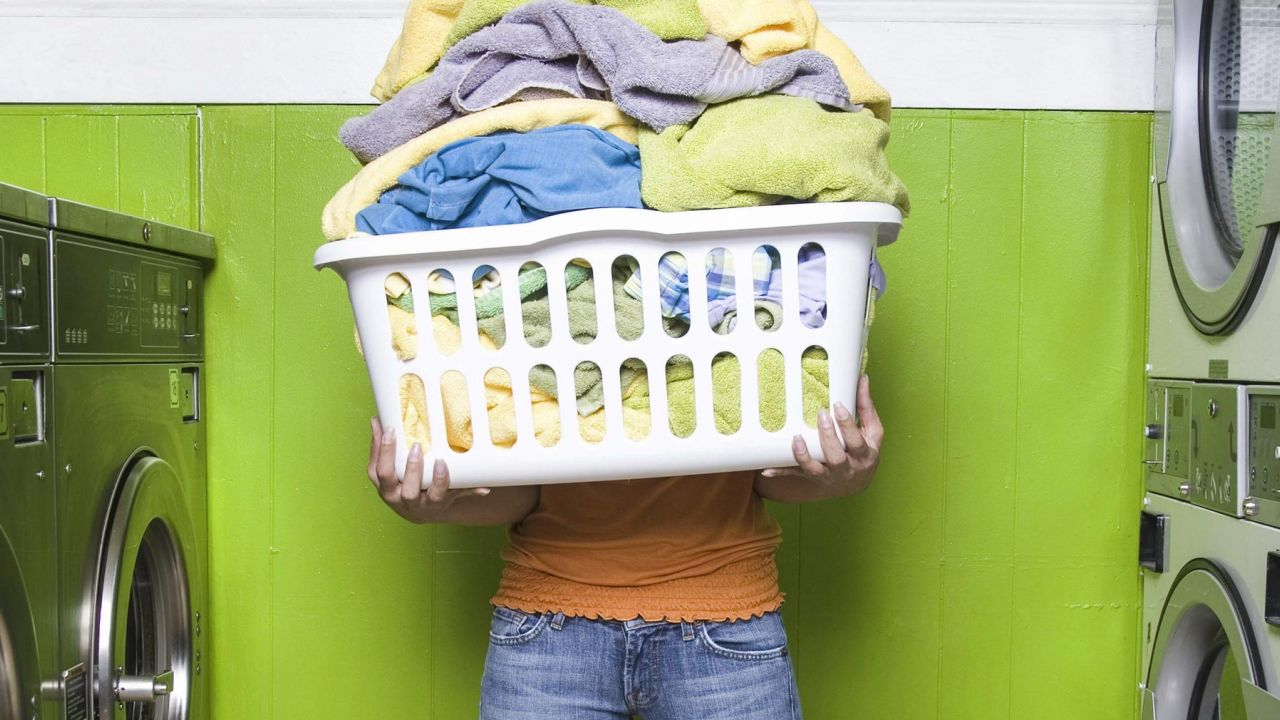 Holding overflowing washing basket at laundrette