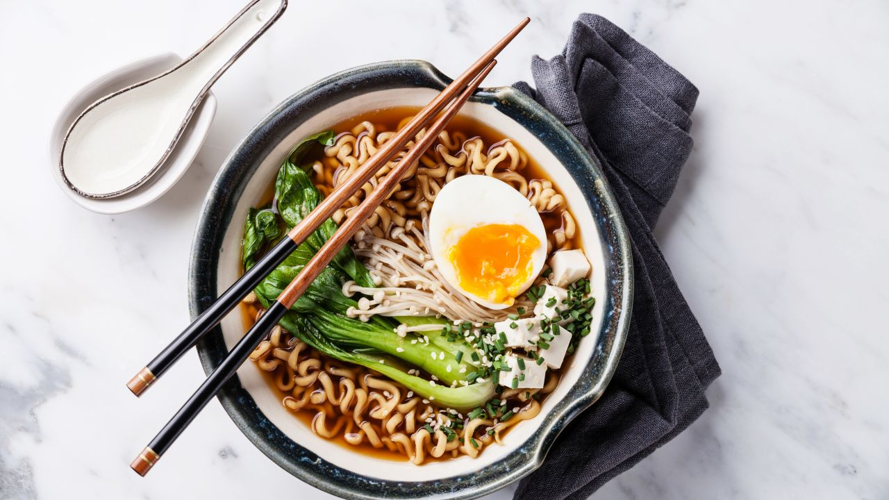 A bowl of noodles with broth, vegetables, and half a boiled egg.
