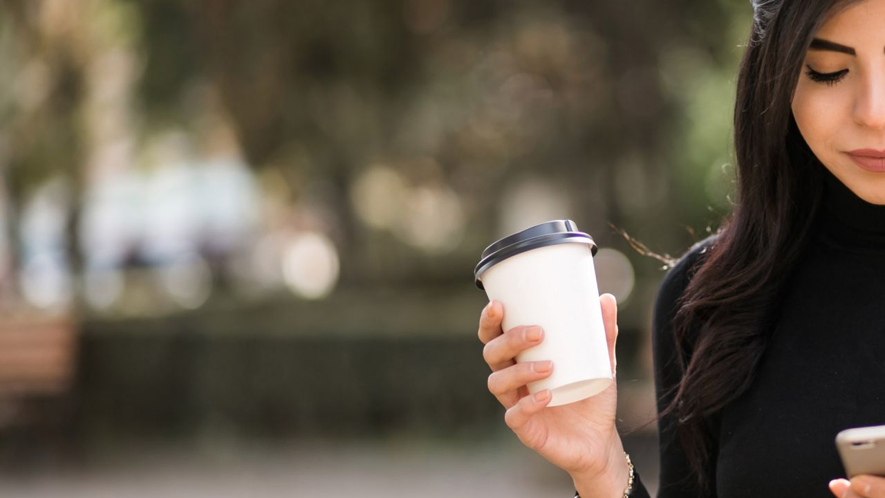 Woman holding takeaway cup while looking at phone