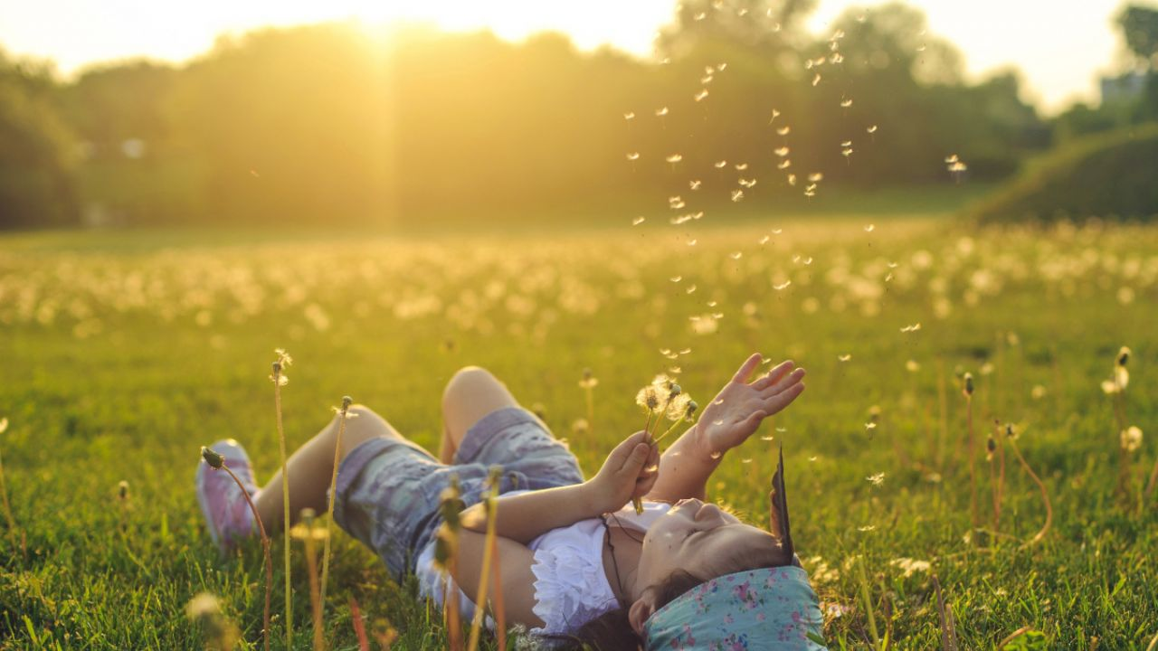 Young girl lying down on a field blowing dandelion seeds