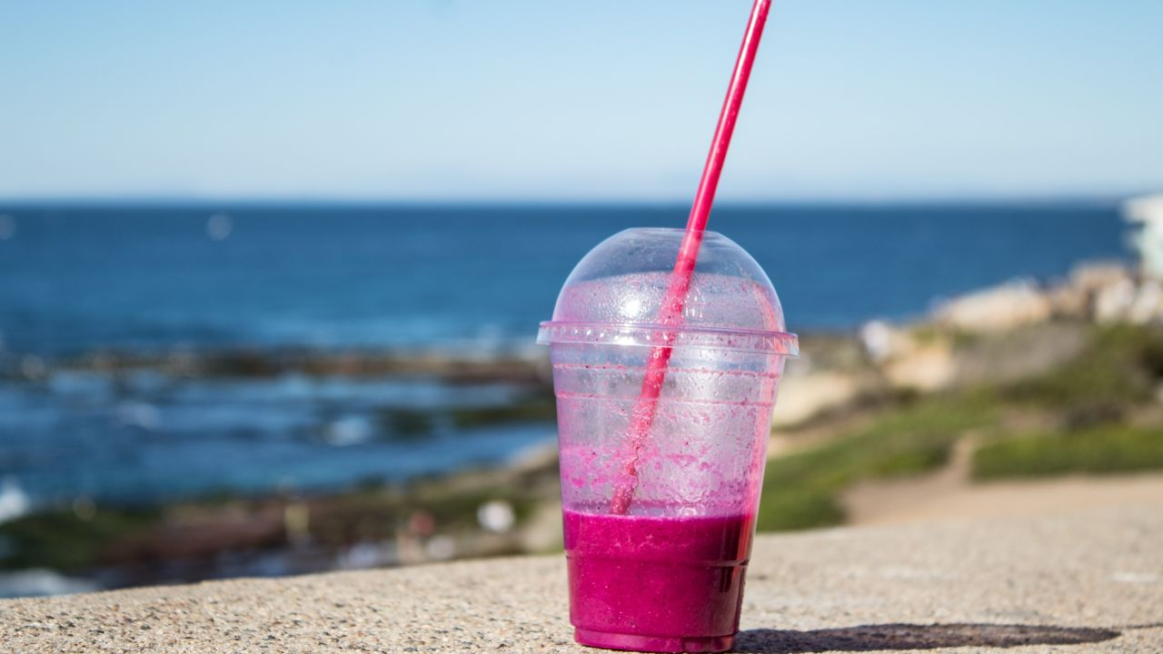 photo of smoothie in plastic cup with lid and straw