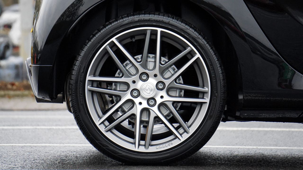 A close up of a tyre on the back wheel of a black car
