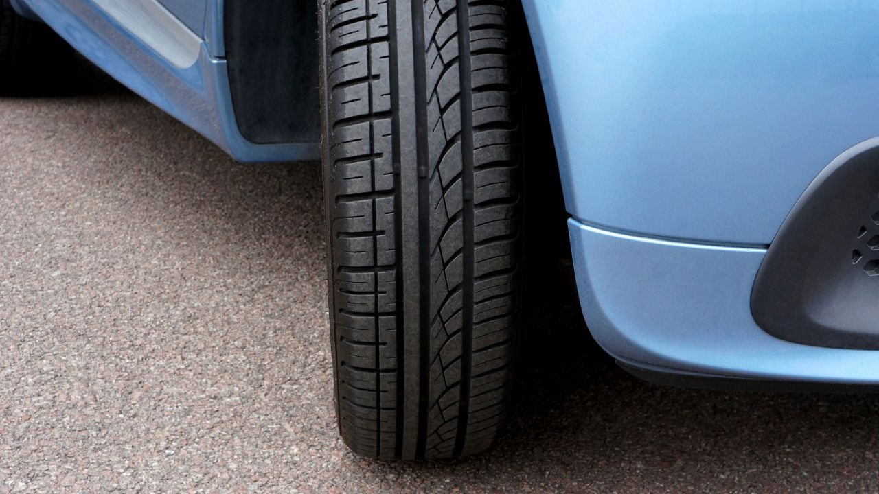 Close up of the front right tyre of a nondescript blue car