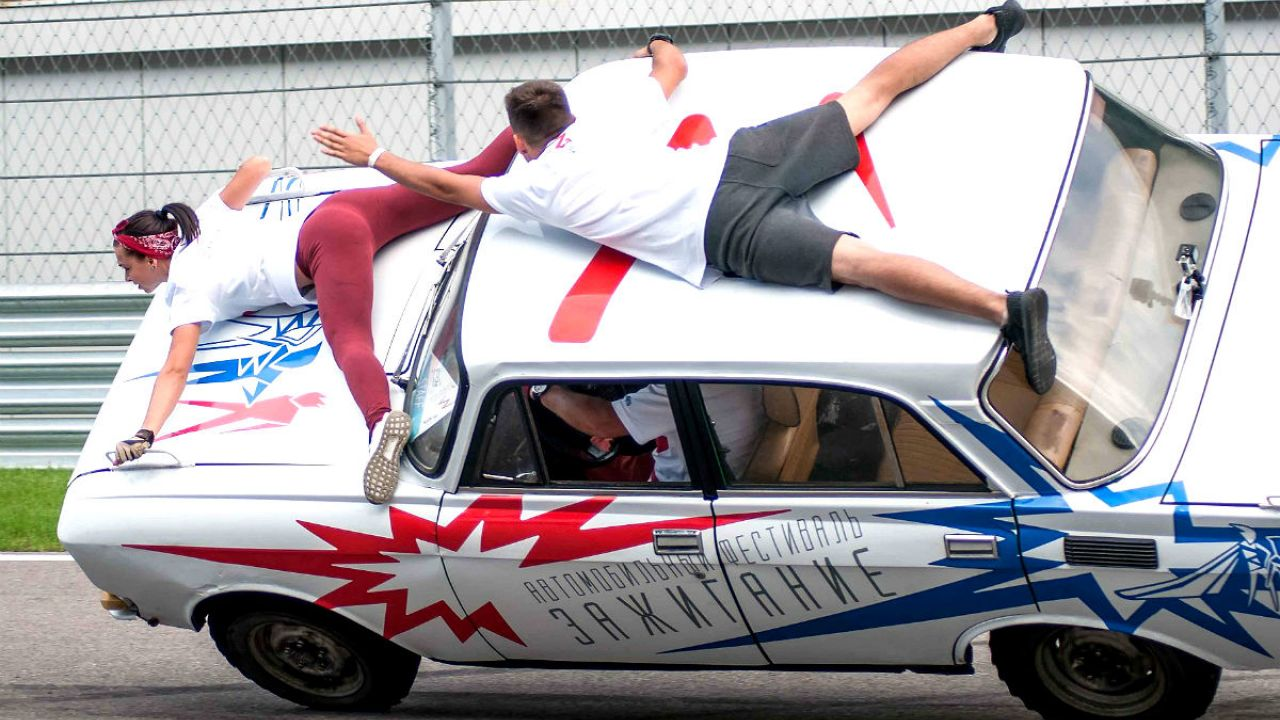 Acrobatics holding on to the top of a car while it races on two wheels tilting to the side