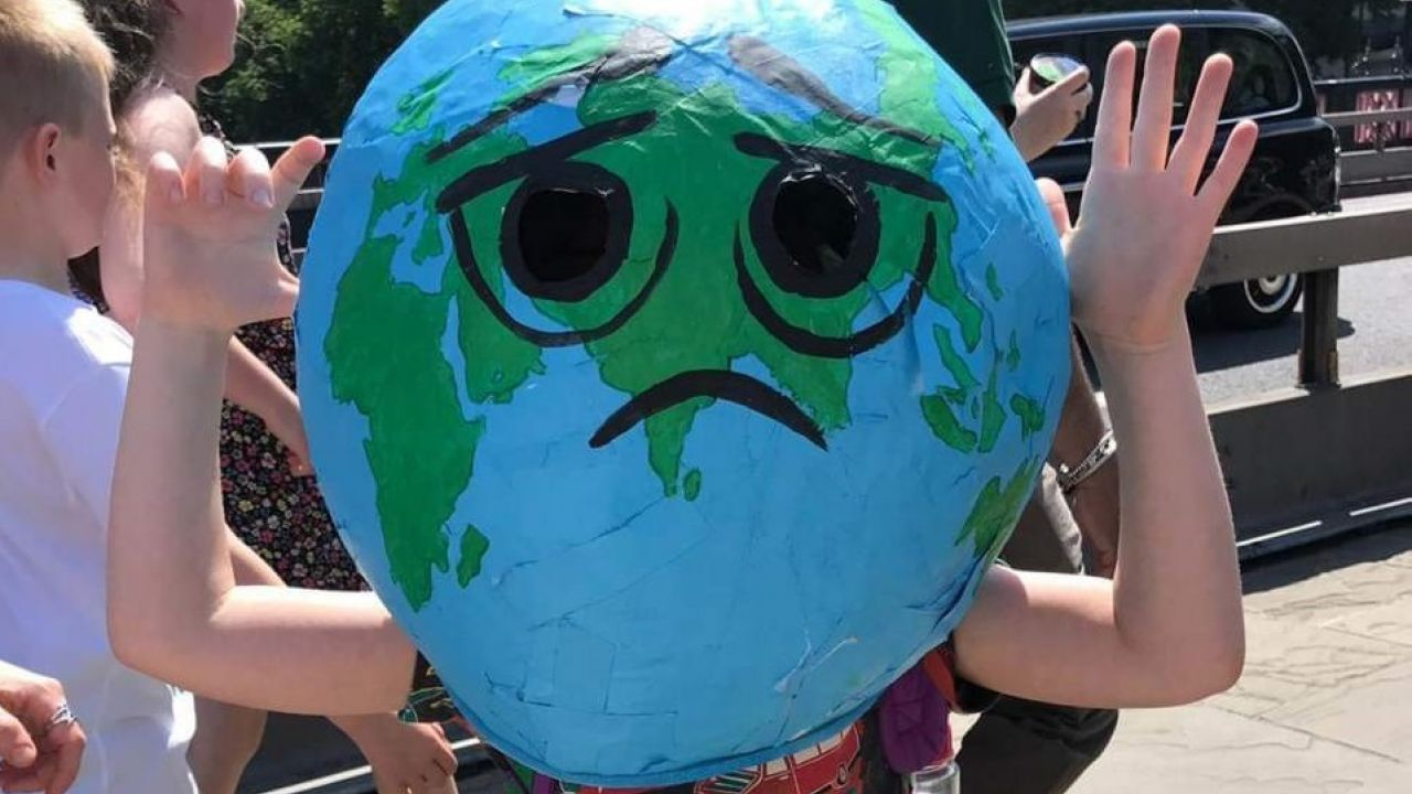 Child wearing Earth head prop