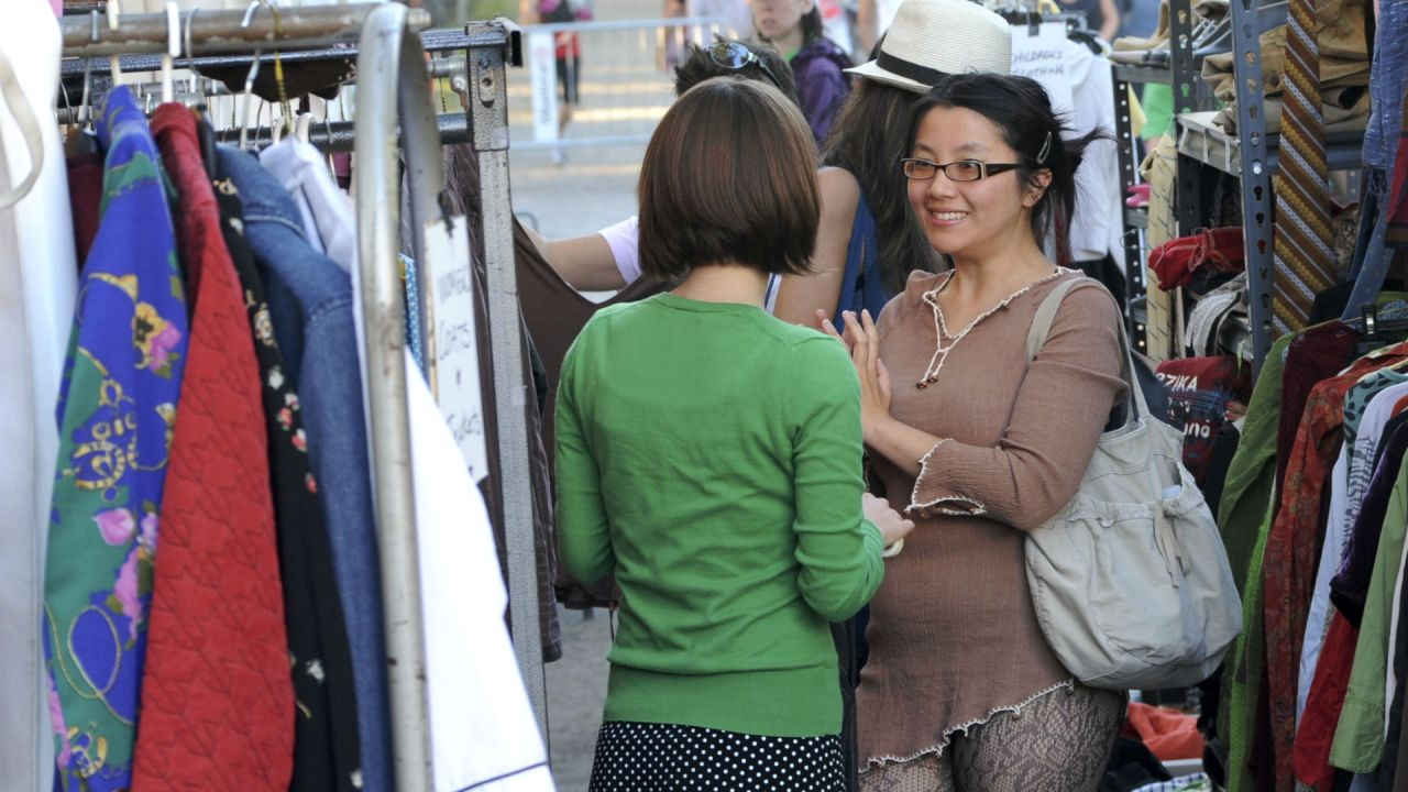 Two women talking at an outdoor clothes swapping event