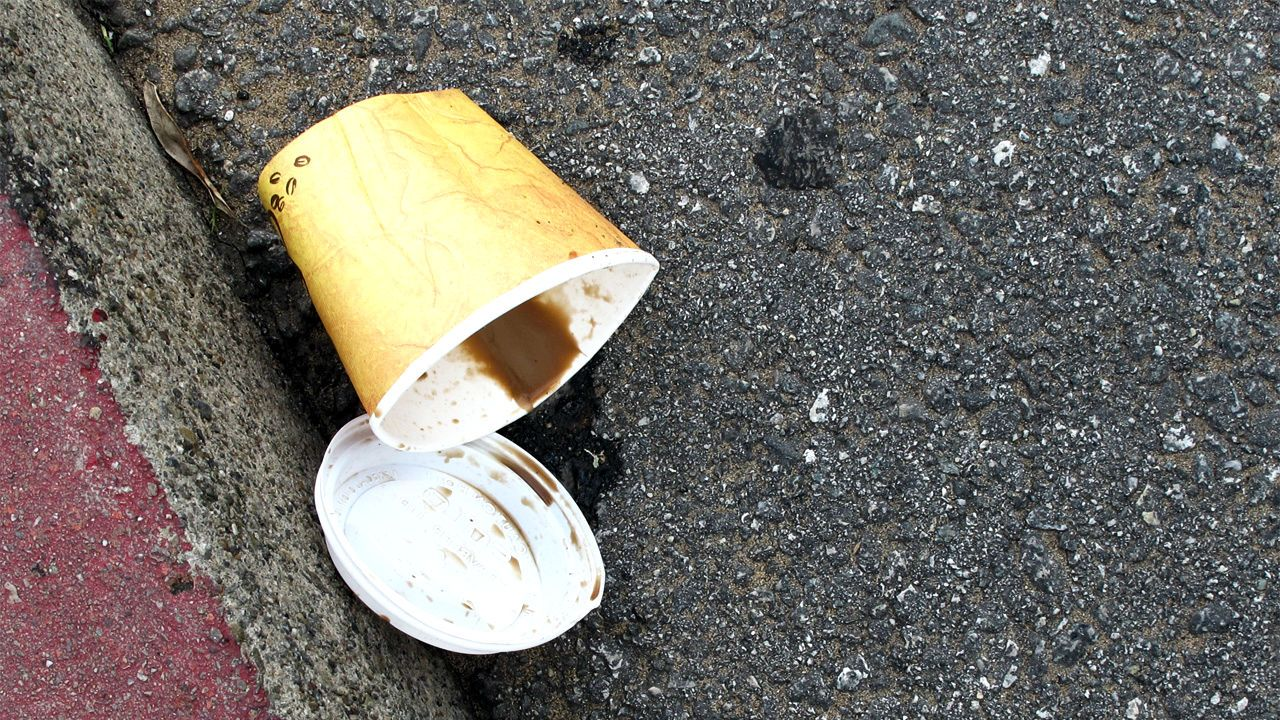 A discarded coffee cup lies on the curb with the remnants of the drink spilling out