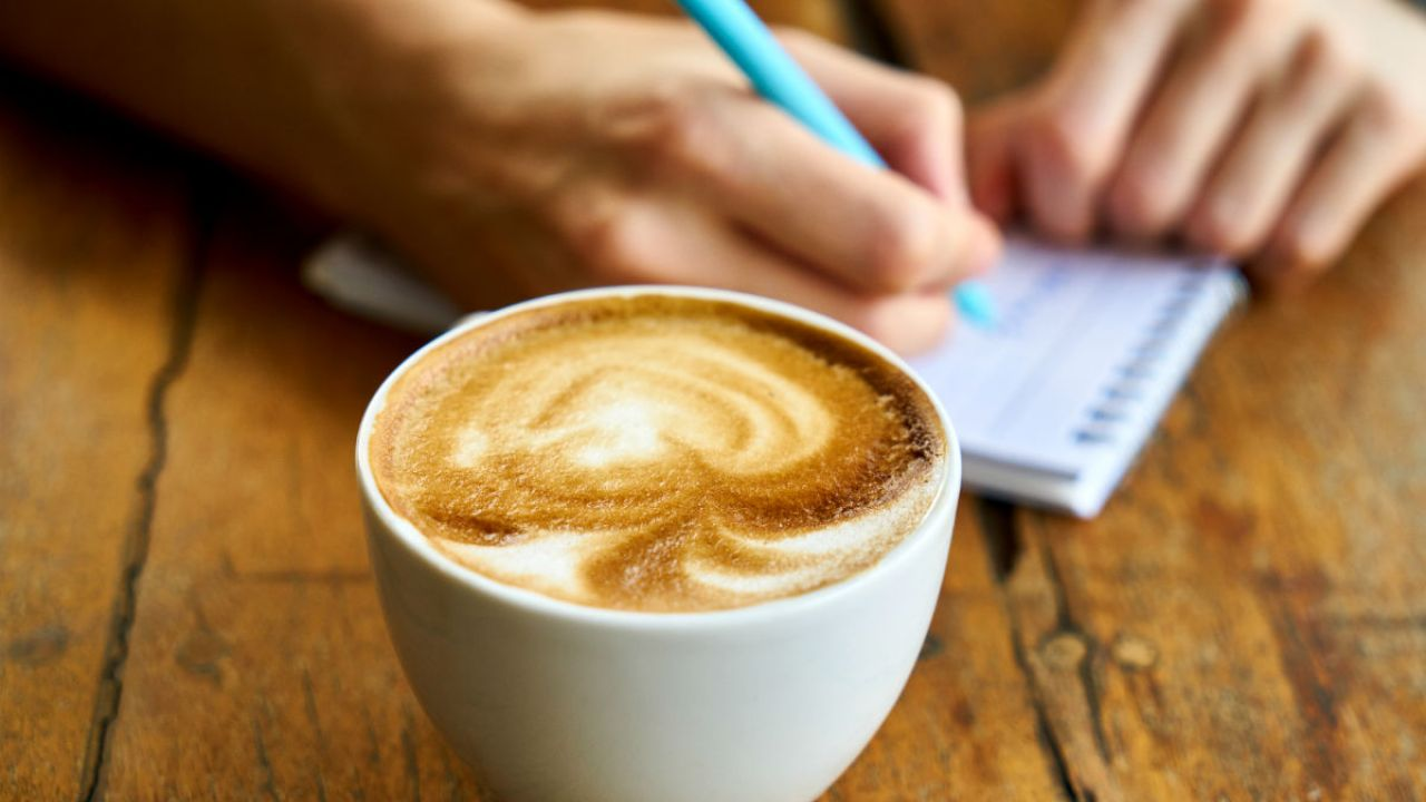 A close up of a man writing in a notepad with a cup of cappuccino
