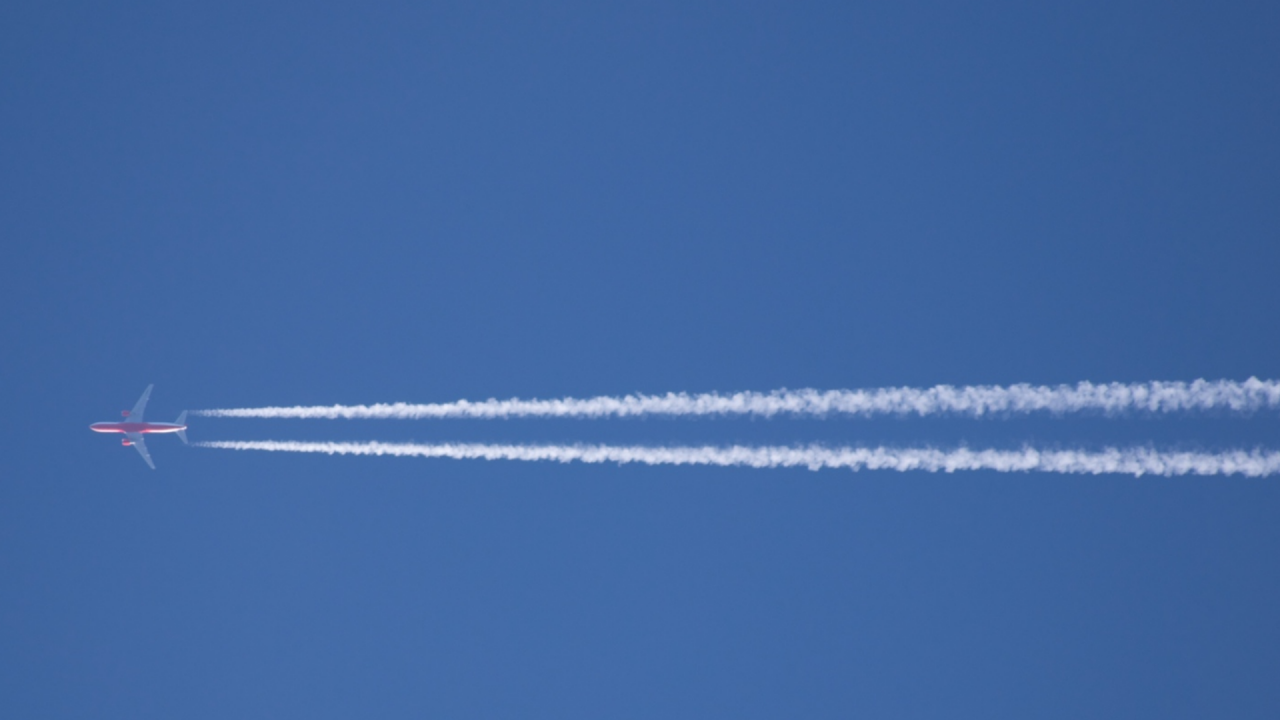 Aeroplane flying across the sky with vapour trail