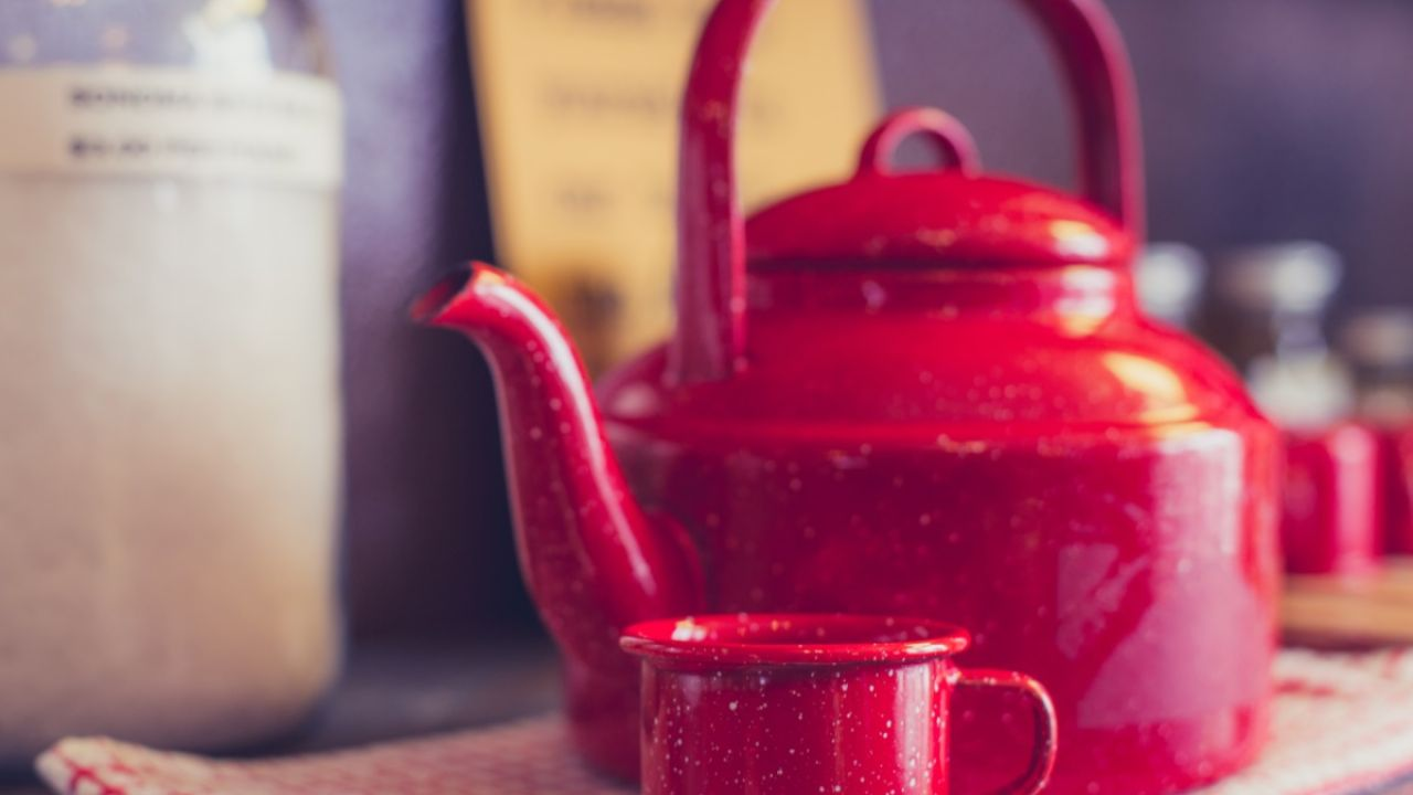 Old red metal kettle with small red metal cup