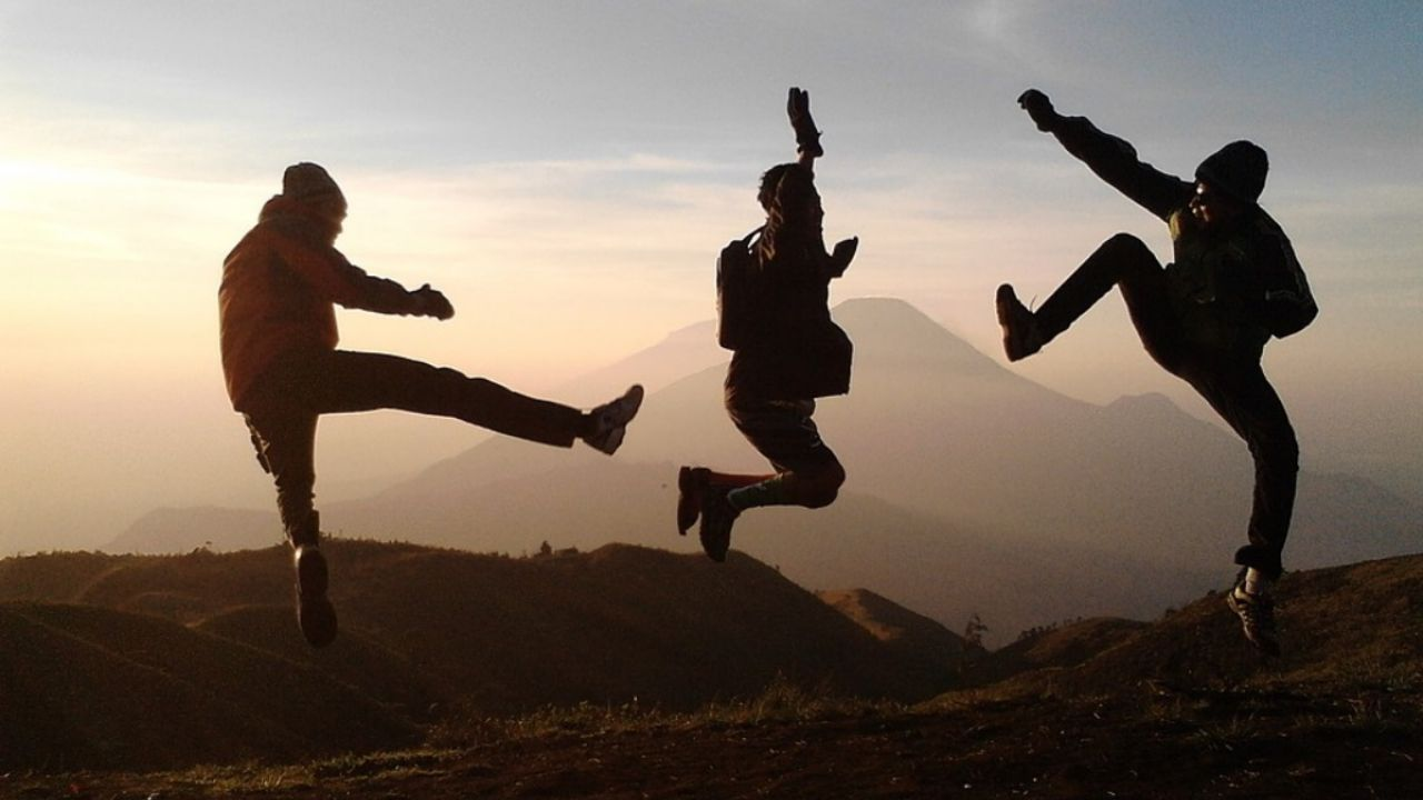 Teenagers jump on a hillside