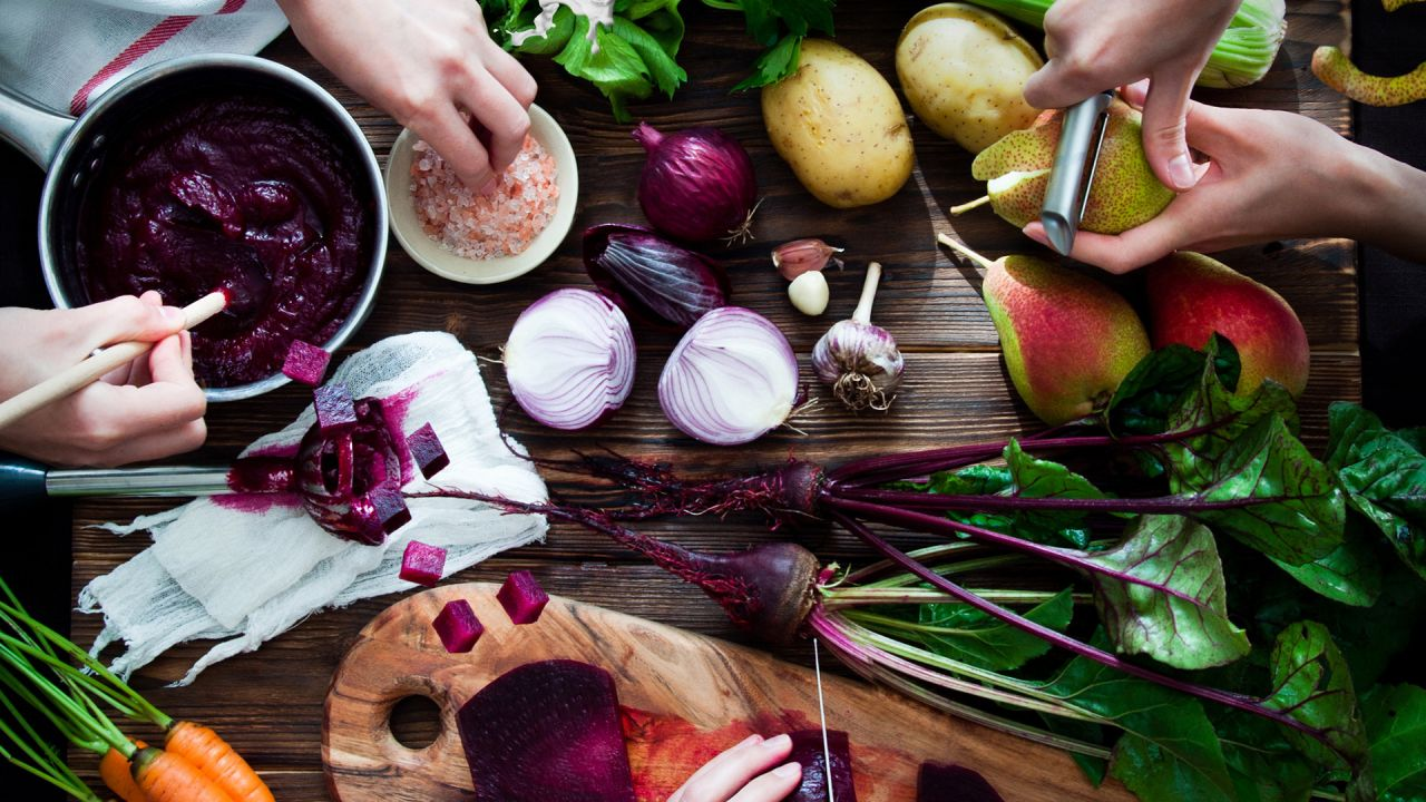 Beetroot, potatoes, onions, pears garlic and carrots on a vibrant chopping board
