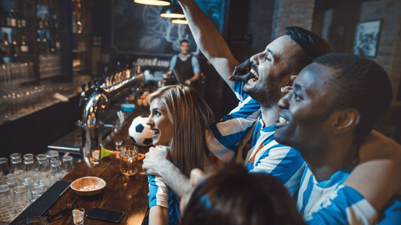 football fans cheering their team on in a bar