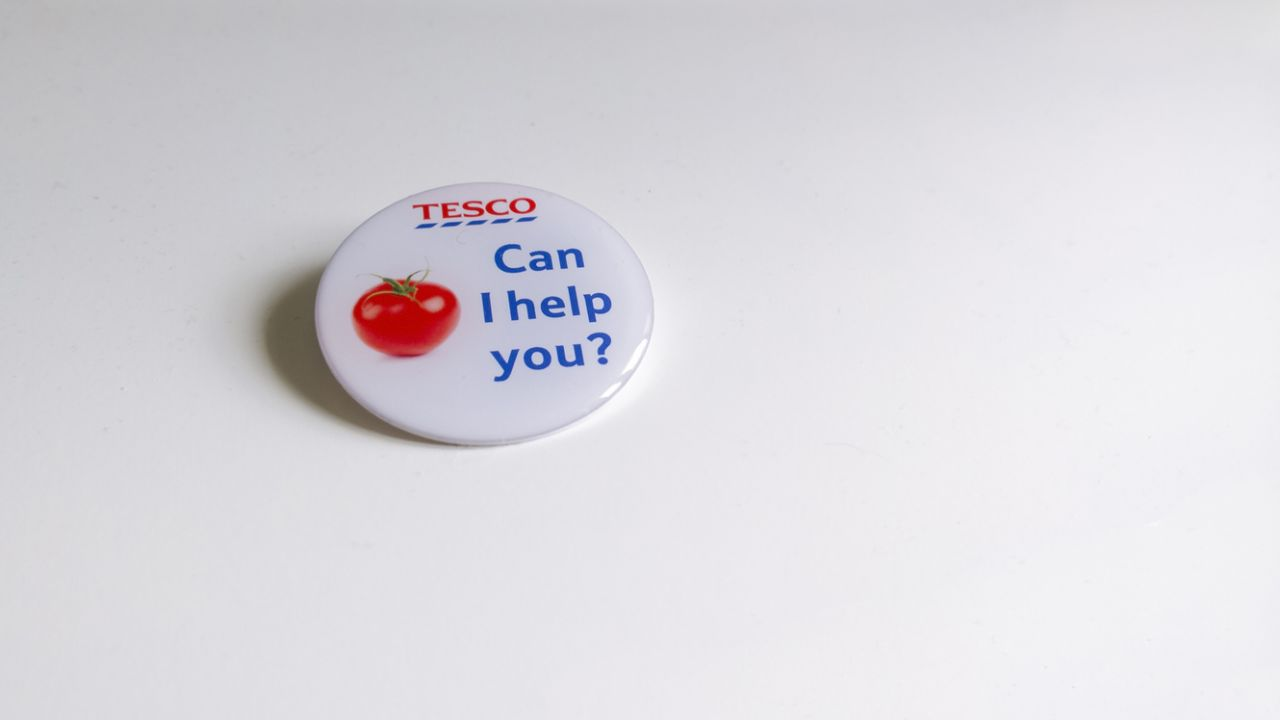 Photo of Tesco-branded badge reading 'Can I help you?'