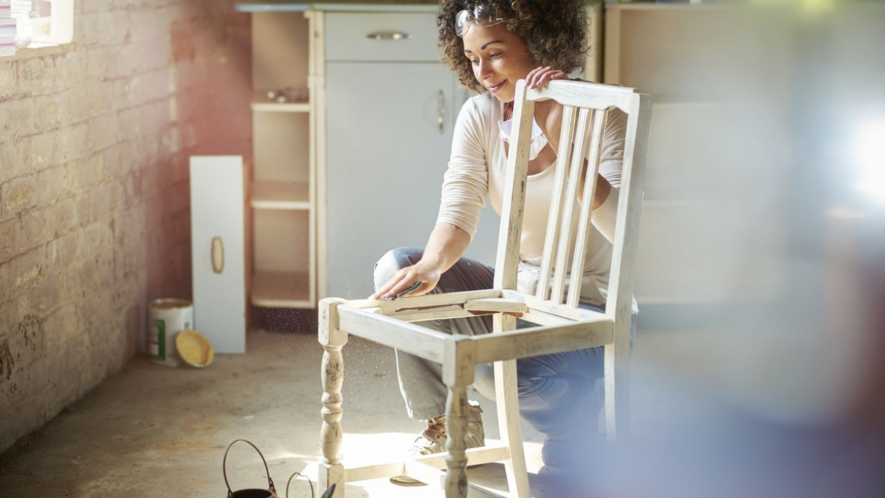 photo of woman sanding wooden chair